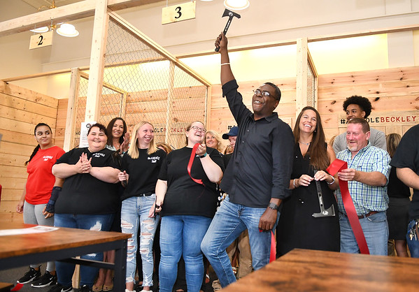 Tony Martin, holding axe in air and April Cook, right of Martin, co-ownwers of Axe Hole, cut the ribbon to open their business Monday afternoon on 328 Neville Street in Beckley.<br /> (Rick Barbero/The Register-Herald)