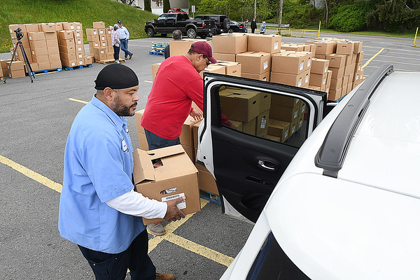 George Webster, Beckley Housing Authority, left, and Ballard Johnson, volunteer, load boxes of food during Farmers to Families food giveaway held Friday from noon until 4 p.m. at the Beckley-Raleigh County Convention Center. 1200 boxes of food that was supplied contain fresh produce, meat and dairy products.<br /> (Rick Barbero/The Register-Herald)
