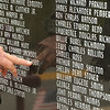 Attendees of the Memorial Day service at Stoco point out names of people that they know that grace the memorial located in Coal City. Jon C. Hancock/for The Register-Herald