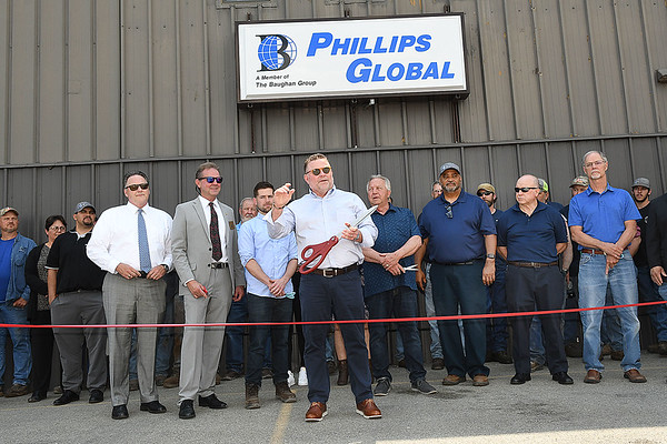 Roger Baughhan, chairman & CEO,Phillips Global, center with scissors, speaks during their Open House and Ribbon Cutting Ceremony held at the plant on George Street in Beckley. The Baughan Group is pleased to announce the purchase of Phillips Machine assets. The Baughan Group's mining companies; Gauley-Robertson, CAI Industries and RiJa, Inc., with this acquisition have consolidated into one company called Phillips Global. Phillips Global and will service customers domestically and internationally with a broad range of products, goods and services. <br /> (Rick Barbero/The Register-Herald)