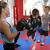 Hope McNeely, owner of A-Train Boxing & Fitness Studio in Mullens, left, working with her students, Liam Howell and Noel Boothe in her gym.<br /> (Rick Barbero/The Register-Herald)