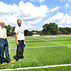 Director of Raleigh County Secondary Schools Eric Dillon, left, and Shady Spring head football coach Vince Culicerto, look over the new turf getting laid down at Shady Spring High School football field. Raleigh County Schools Superintendent David Price said the field would be ready for Friday's home game against Tug Valley. Crews from The Motz Groupare are laying the turf and PCM Contractor from Sophia are working on the bleachers. Price said, they are are adding wheel chair ramps and seating for the handicap and also placing new handrails in each section of the bleachers. The visitor bleacher will not be completed by kickoff Friday, but will have designated seating for the opposing team.<br /> (Rick Barbero/The Register-Herald)