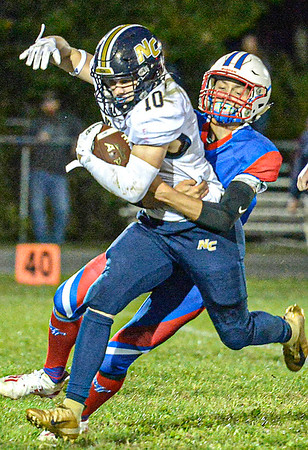 F. Brian Ferguson/Register-Herald Nicholas County's Kaleb Clark picjs up fround yards as Midland Trail's Zachariah Baird makes the stop during Friday action in Hico.