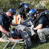 Members of Alpha Metallurgical Resources help a injured miner in a mine simulated explosion during the Fallen Heroes Mine Rescue Contest held at Sylvester Pavilion Park in Boone County. Ten mining compnay teams competed to solved hypothetical mine-related problems while being timed and observed by judges. The contest is intended to promote mine safety by sharpening the skills of miners who may be called to respond to a mine emergency in the future.<br /> (Rick Barbero/The Register-Herald)
