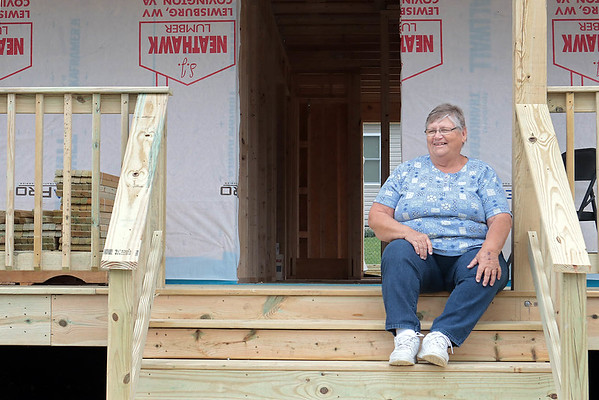 Dottie Fisher sits on the porch of her new  home in Hope Village in White Sulphur Springs Thursday. Fisher's home was destroyed by a fire and Storm-Aid, the Amish group that constructed the houses in the wake of the flood - has come to rebuild it. Jenny Harnish for the Register-Herald