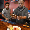 Dinesh Lamichhane, left, watching Robert Jones prepare Avocado Toast and Fruit & Vegetable Bowl at Jimmie's Place on South Kanawha Street in Beckley.<br /> (Rick Barbero/The Register-Herald)