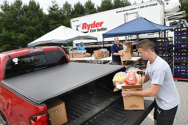 Dakota Bouvy, volunteer Life Changers Oureach, loads one of 150 boxes of food during the Mountaineer Food Bank Mobile Food Pantry food giveaway. Canned beef & chicken, milk, produce boxes and bread was handed out from 11 am to 1 p.m. at Lester Elementary School.<br /> (Rick Barbero/The Register-Herald)