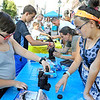 (Brad Davis/For The Register-Herald) Eleven-year-old teammates Olivia Horton, nearest right, and Dominic Drennen, nearest left, take on four other teams of all ages in the prestigious Oreo cookie stacking contest during Appalaichain Festival Street Fair action Saturday night in downtown Beckley.