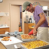 Good Roads Bakehouse owner Daniel Cannon cuts some focaccia on opening day of his new bakery in Frankford Saturday. Jenny Harnish/The Register-Herald