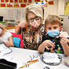 Lora Griffith kindergarten teacher at Pineville Elementary School, center, working with her students, Brinley Brooks, left, and Ian Fischer on the letter P by making paper penguins.<br /> (Rick Barbero/The Register-Herald)