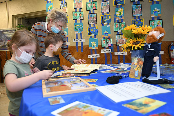 Adalyn Young, left, and Everett Luckie, with their teacher Jane Atinson, pre-k class at St. Francis de Sales school in Beckley, look over materials the Vangogh exhibit they helped create for their annual fund raising art gallery that's on display in the school. Atinson said, this was a two month project with students producing 400 pieces of art that are displayed in 15 seperate exhibits. Members of the church, staff members, students. parents and grandparents are able to view the gallery Thursday and Friday in the parish hall between 8 am and 2:30 p.m. and can purchase a piece of artwork in a frame for $10.  The fund raiser helps to buy art supplies and other activities.<br /> (Rick Barbero/The Register-Herald)
