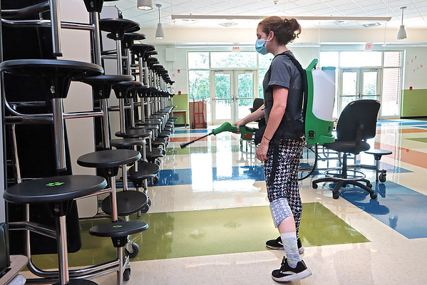 Lewisburg Elementary School custodian Melissa Baker demonstrates an Electrostatic Backpack Sprayer in the school in Lewisburg Monday. The backpack is one of the many items purchased with federal grant money that became available to the nation's school systems throughout the pandemic. The sprayer is an efficient disinfecting solutions for large areas such as classrooms and cafeterias. Jenny Harnish/The Register-Herald