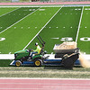 Crew from The Motz Group spreading sand on the new turf at Shady Spring High School football field Monday afternoon. Raleigh County Schools Superintendent David Price said, crews are working on the turf and adding wheel chair ramps and seating for the handicap and also placing new handrails in each section of the bleachers. The visitor bleacher will not be completed by kickoff Friday, but will have designated seating for the opposing team.<br /> (Rick Barbero/The Register-Herald)