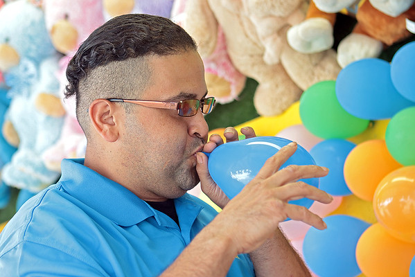 Fair worker Daniel Torres blows a balloon at the State Fair of West Virginia Wednesday. Torres has been working the fair for the last twenty years. Jenny Harnish/The Register-Herald