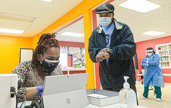 Cresia Davis, left, checks in Charles Christian, 63, of Beckley, during Wednesday's Covid testing at the Multicultural Center in Beckley. <br /> F. Brian Ferguson/for The Register-herald