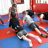 Hope McNeely, owner of A-Train Boxing & Fitness Studio in Mullens, and her class doing push-up during a workout in her gym.<br /> (Rick Barbero/The Register-Herald)