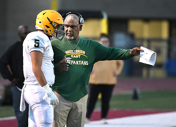 Branden Bragg, of Greenbrier East, left, has a conversation with head coach Ray Lee during game against Woodrow Wilson at VanMeter Stadium in Beckley Friday night.<br /> (Rick Barbero/The Register-Herald)