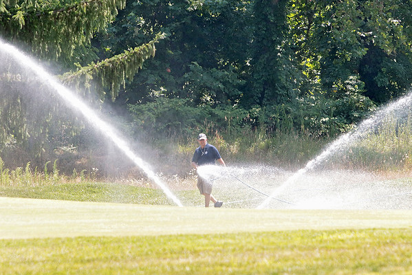 A groundskeeper waters the grounds of the Greenbrier during the 102nd West Virginia Amateur on the Old White course in White Sulphur Springs Wednesday.   Jenny Harnish/ The Register-Herald