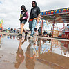 Fair goers walk through a puddle at the State Fair of West Virginia in Fairlea Monday. Rain is in the forecast for most of the week. Jenny Harnish/The Register-Herald