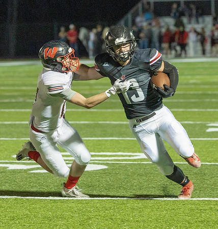 Logan Doddrill for Liberty stiff arms the defenter for postive yards Friday night against Wayne.<br /> Tina Laney/for The Register-Herald