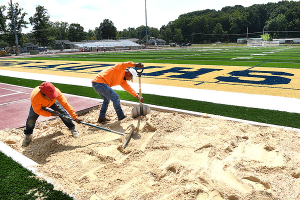 Peter Rubin, left, and Brison Barcenas, from The Motz Group, working on the sand pit near the endzone of Shady Spring football field Monday afternoon. Raleigh County Schools Superintendent David Price said, crews are working on the turf and adding wheel chair ramps and seating for the handicap and also placing new handrails in each section of the bleachers. The visitor bleacher will not be completed by kickoff Friday, but will have designated seating for the opposing team.<br /> (Rick Barbero/The Register-Herald)