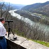 Ben Markell, of Princeton, viewing a bald eagle with her two babies in a nest through his telescope at the Brooks overlook in Summers County. Markell returns to the area every year viewing the eagles across the river on the downstream end of Brooks island in a large sycamore tree is a nest built by the first confirmed breeding pair of eagles in the New River Gorge National River. The Nest was started in the winter of 2009 and the eagles have returned to the area every winter since.<br /> (Rick Barbero/The Register-Herald)