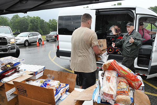 Greg Brown, volunteer Life Changers Oureach, left, and Steve Tanner, volunteer, load one of 150 boxes of food in a van during the Mountaineer Food Bank Mobile Food Pantry food giveaway. Canned beef & chicken, milk, produce boxes and bread was handed out from 11 am to 1 p.m. at Lester Elementary School.<br /> (Rick Barbero/The Register-Herald)