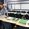 Kathy Neil 4th grade teacher at Maxwell Hill Elementary School puts materials on her students desk for the first day of school that starts Tuesday in Raleigh County.<br /> (Rick Barbero/The Register-Herald)