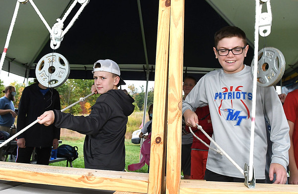 Midland Trail Middle school Students, Samuel Shumate, left, and Jaxon Barnhouse, learning the science involving archery by using the demo pully system during WVU Adventure School head at the Summit Bechtel Reserve in Glen Jean.<br /> (Rick Barbero/The Register-Herald)