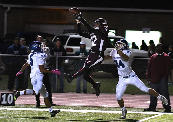 Elijah Redfern, of Woodrow Wilson, center, leaps but can't quite bring in the reception between two Princeton defenders during first half action Friday night at VanMeter Stadium in Beckley.<br /> (Rick Barbero/The Register-Herald)