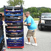 David Jones, volunteer Life Changers Oureach, pushes a rack of bread during the Mountaineer Food Bank Mobile Food Pantry food giveaway. Canned beef & chicken, milk, produce boxes and bread was handed out from 11 am to 1 p.m. at Lester Elementary School.<br /> (Rick Barbero/The Register-Herald)