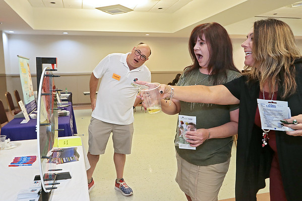 Paula Shrewsberry and Kim Fry, left, react after spinning a wheel of fortune from Mighty Shine Car Wash at the Business After Hours at the Beckley Raleigh County Convention Center Thursday. Jenny Harnish/The Register-Herald