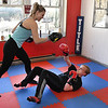 Hope McNeely, owner of A-Train Boxing & Fitness Studio in Mullens, teaching Joshua Tilley how to defend himself on his back.<br />  (Rick Barbero/The Register-Herald)