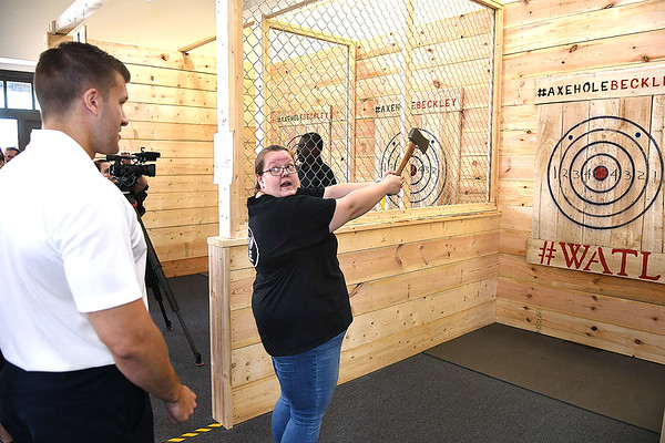 Ben Spurlock, left, gets instructions from Lindsey Pratt, axe pro, on how to throw an axe at the Axe Hole on 328 Neville Street in Beckley.<br /> (Rick Barbero/The Register-Herald)