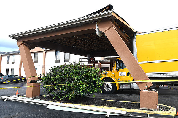 Truck crashed into the canopy at the entrance of Howard Johnson Express Inn off of Harper Road Monday evening. Manager Shelia Warren said, the clearence to get through is 14.6 feet which was to low for the truck to enter. Construction Management Group from Daniels was on scene to take down the structure.<br /> (Rick Barbero/The Register-Herald)
