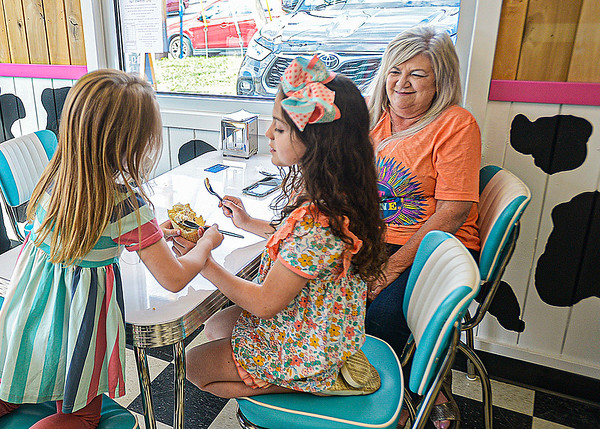 Lacey Treadway, 5, and Adalyn Queen, 8, enjoy ice cream at the Frozen Barn as grandmother, Becky Lilly, right, looks on. F. Brian Ferguson/for The Register-herald