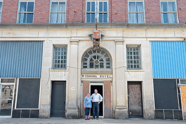 Mullens Community Development Corporation President Carolyn Wilcox and Executive Director of Peacework stand in front of the Wyoming Hotel in Mullens Thursday. The building, which has stood empty since the 1980's, was donated to the town and several organizations would like to see it restored to a hotel and restaurant. Renovations on the building will begin in September, but additional funding is needed to complete the project. Jenny Harnish/The Register-Herald