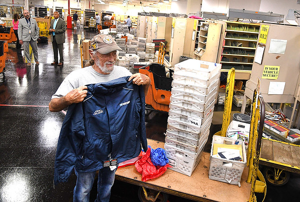 Postal Clerk John Obugene holds up a postal jacket that was presented to him for his 50 years of dedicated service at a special ceremony on Wednesday, August 11, at Beckley Post Office on 134 Industrial Dr. Obugene's family members, coworkers, and several former coworkers attended the surprise event.<br /> (Rick Barbero/THe Register-Herald)