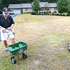 Roger Mitchem, of Beckley, speads Sevin Insect Lawn Granules to kill Army Worms that has invaded his yard on 209 Timber Ridge Drive.<br /> (Rick Barbero/The Register-Herald)