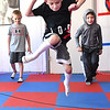 "From left, Noel Boothe, Liam Howell and Elijah Cochran, are being taught timing event called ""Jump the Snake"" by Hope McNeely, owner of A-Train Boxing & Fitness Studio in Mullens.<br /> (Rick Barbero/The Register-Herald)"