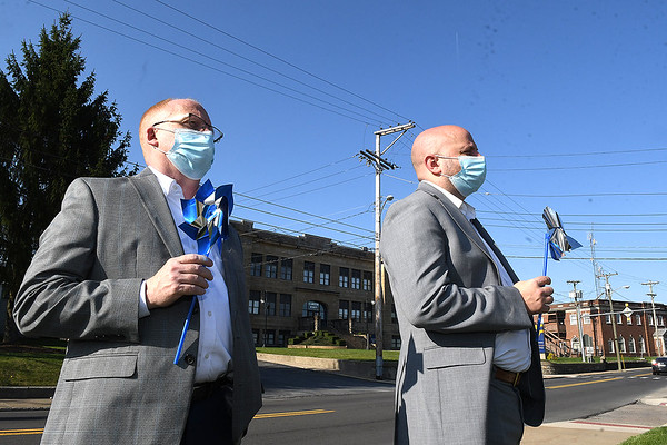 Raleigh County special investigator Jeff Shumate, left and prosecuting attorney Ben Hatfield, listens to Beckley mayor Rob Rappold proclaim April as Child Abuse Prevention and Awareness month on the front lawn of the mayors office on South Kanawha Street in Beckley Tuesday morning.<br /> (Rick Barbero/The Register-Herald)