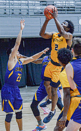 Carlow University's Eric Truong, left, defends as WVU Tech's Darrin Martin drives for the score during Friday evening action in Beckley. F. Brian Ferguson