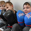 Noel Boothe, left, Liam Howell and Eligah Cochran, waith their turn during their clas with Hope McNeely, owner of A-Train Boxing & Fitness Studio in Mullens. <br /> (Rick Barbero/The Register-Herald)