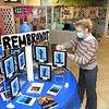 Jane Atinson, pre-k teacher St. Francis de Sales school in Beckley, arranges artwork in the Rembrandt's section her students produced for their annual fund raising art gallery that's on display in the school. Atinson said, this was a two month project with students producing 400 pieces of art that are displayed in 15 seperate exhibits. Members of the church, staff members, students. parents and grandparents are able to view the gallery Thursday and Friday in the parish hall between 8 am and 2:30 p.m. and can purchase a piece of artwork in a frame for $10.  The fund raiser helps to buy art supplies and other activities.<br /> (Rick Barbero/The Register-Herald)