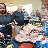 Kanesha Moore, left, from Forever Clean, and Martha Wilkinson President of the Beckley Concert Association visit the buffet at Business After Hours at the Beckley Woman's Club Thursday. The Beckley Concert Association is back after being shut down last year because of COVID.  Jenny Harnish/The Register-Herald.