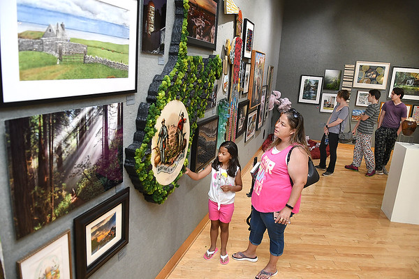 Mikylah Ferrell, 7, with her mother Carolyn Griner, of Bridgeton, NJ, looks over the Best of West Virginia 13th Annual Open Juried exhibit displayed in the gallery at Tamarack. Ninety five artist from all over the state displayed 125 pieces of artwork that was juried by Elaine Gustafson and Ron Donoughe. Best of show was awarded to Coal Camp, by Patty Wolford, second place- Looking Back, by Richard Shrewsberry and third place- Swim in Pure Drinking Water, by Michael Teel. People Choice will be awared when the show closes out on August 1.<br /> (Rick Barbero/The Register-Herald)