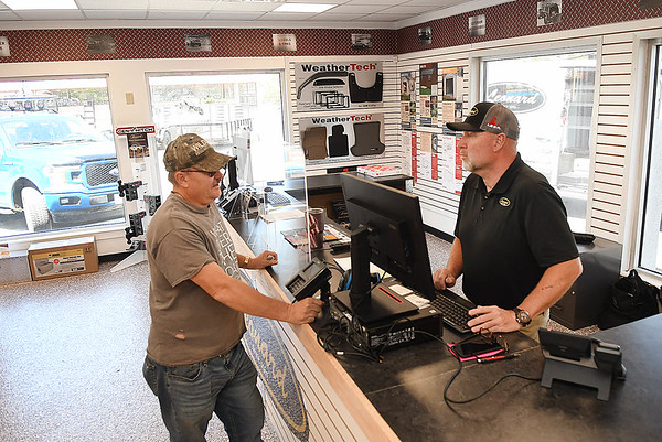 Ken Parent, manager, of Leonard Building Truck & Accessories on 3788 Robert C Byrd Drive in Beckley, helping his customer, Roy Johnson, of Itman.<br /> (Rick Barbero/THe Register-Herald)