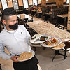 Wuinder Miranda, server Campestre on Harper Road, carries out food from the kitchen.<br /> (Rick Barbero/The Register-Herald)