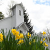 Flowers are now blooming in front of the Coal Camp Church at New River Park in Beckley Thursday afternoon. The church was built in 1921 in the coal camp of Pemberton and coal baron Thomas Hurst Wickham paid to build the church and gave it as a gift to the community.<br /> (Rick Barbero/The Register-Herald)