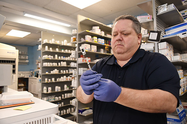 Gary Cunningham, pharmacist of Bypass Pharmacy on Eisenhower Drive prepare a COVID-19 vaccinations.<br /> (Rick Barbero/The Register-Herald)